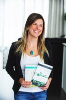 Canadian Author Robyn Liechti wearing green necklace and black blazer smiling holding hardcover guided journals The Making of a Grandparent and The Making of a Grateful Heart