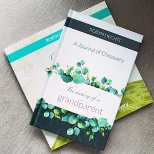 Hardcover journal The Making of a Grandparent stacked on top of books