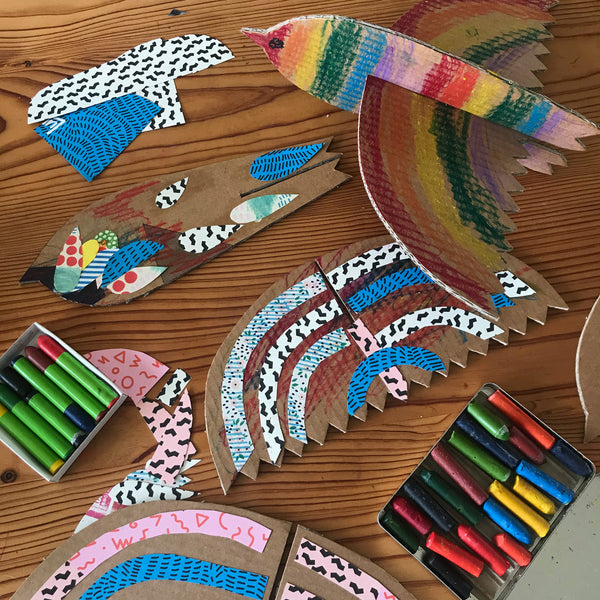 kids cardboard bird craft project and crayons on a table