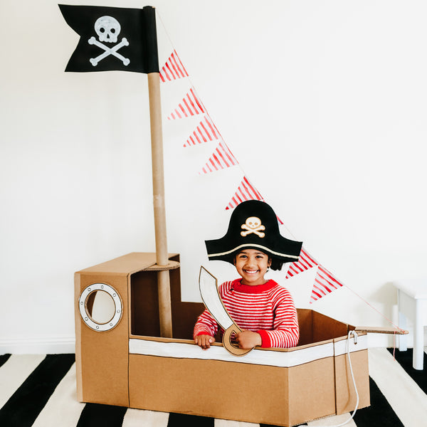 child playing in a cardboard box pirate ship