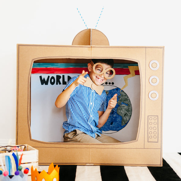 Child playing in a large cardboard box TV