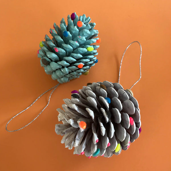 Non-traditional painted pin cone decorations