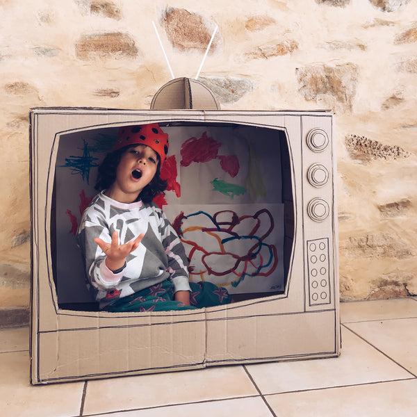 child acting inside a cardboard box TV