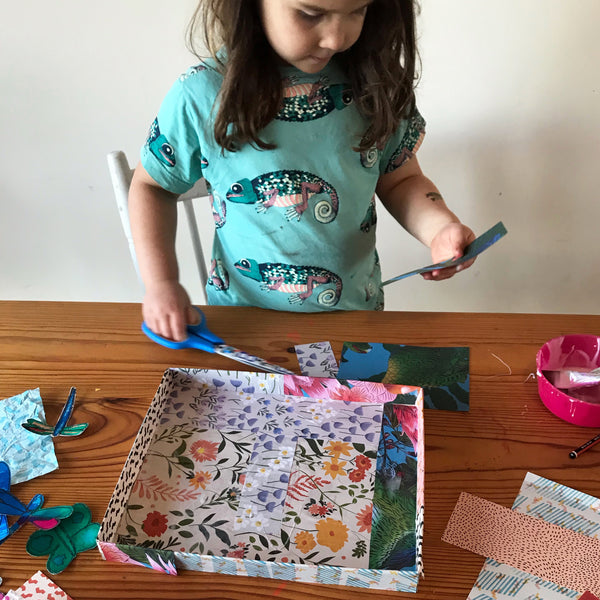 Child decorating a shoe box lid with patterned paper collage