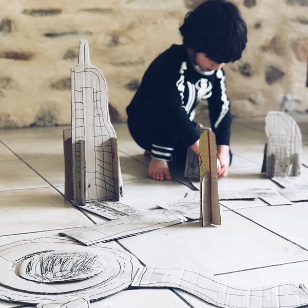 child playing with recycled cardboard city