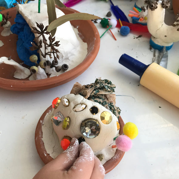 child decorating a clay fairy cave with gems
