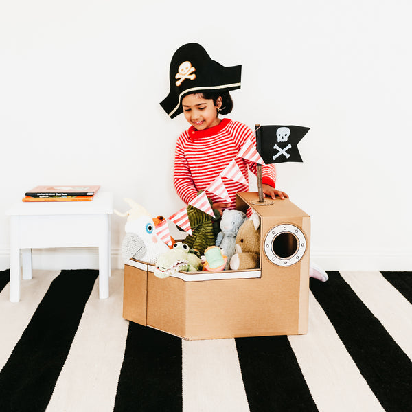 child playing with a pirate ship made from cardboard boxes