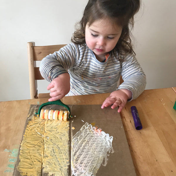 Toddler painting cardboard with a roller