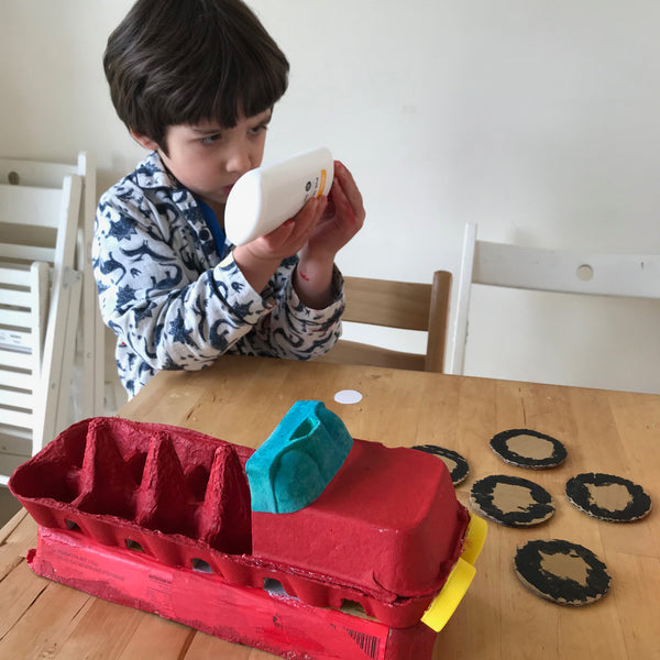 child making a fire engine from egg cartons