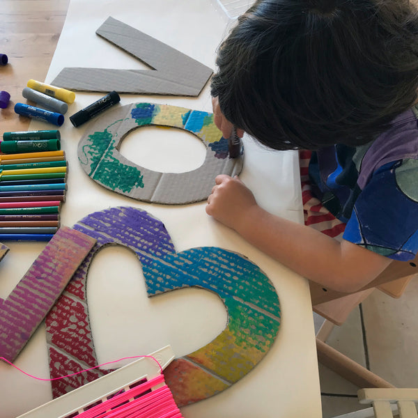 Child colouring in cardboard shapes