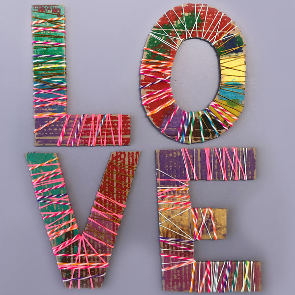 Large cardboard letters wrapped in yarn, wool and cord
