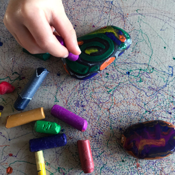 Child decorating hot pebbles with wax crayons