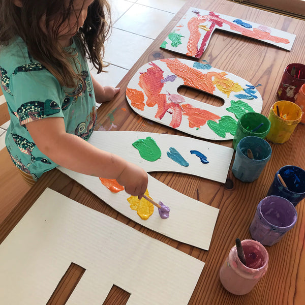 Child painting large cardboard letters