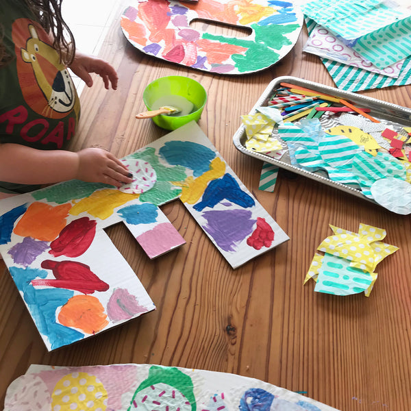 Child adding collage materials to large letters