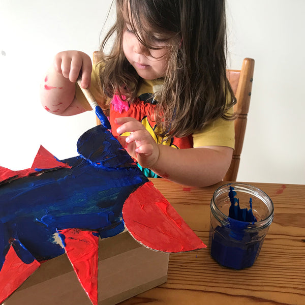 child painting a cardboard box monster