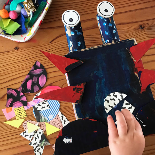 child's hand gluing collage materials to a monster
