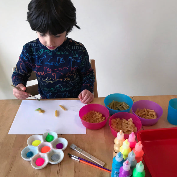 Child painting pasta shapes with paint