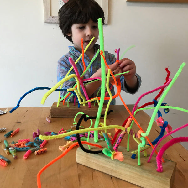 Child threading pasta shapes onto pipe cleaners