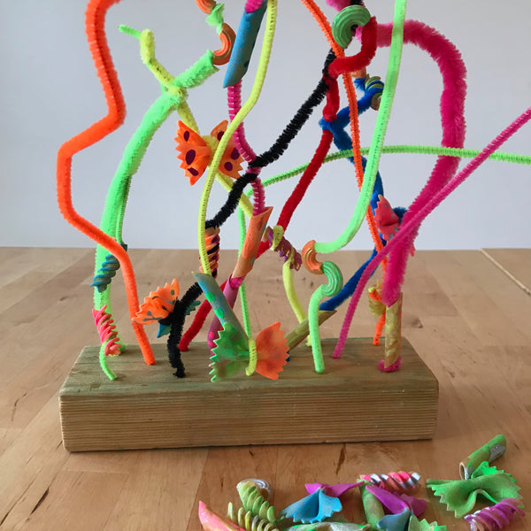 painted pasta sculpture threaded onto pipe cleaners