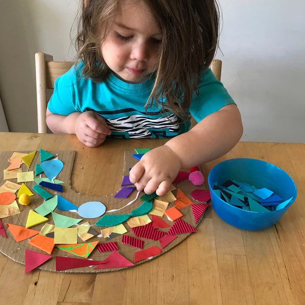 Child making rainbow pattern paper collage