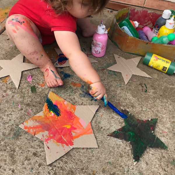 toddler doing messy painting on cardboard stars