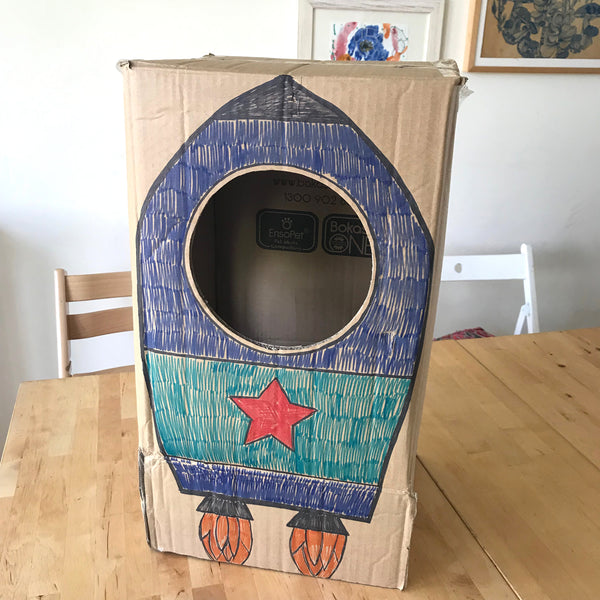 A rocket dress up costume for kids made from a cardboard box