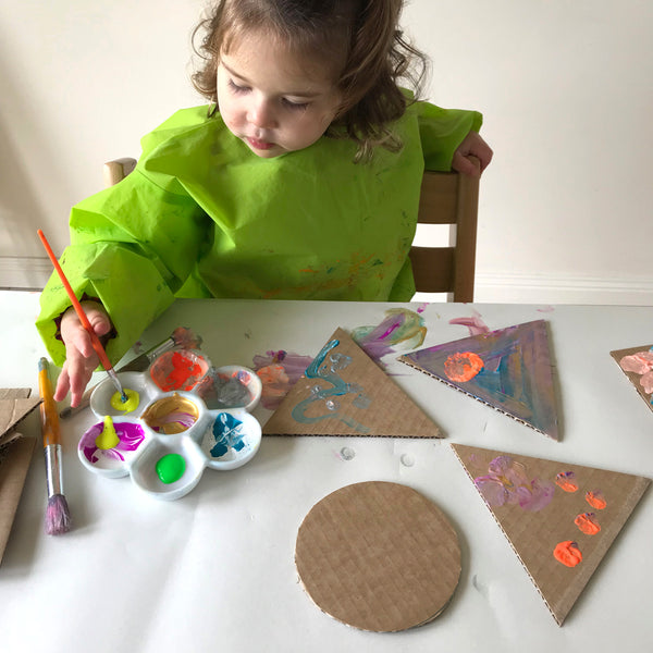 child painting cardboard shapes