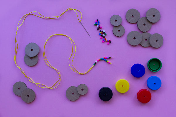 beads, cardboard discs and bottle tops to make a snake marionette