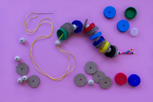 bottle tops and cardboard discs threaded into a string to make a snake puppet