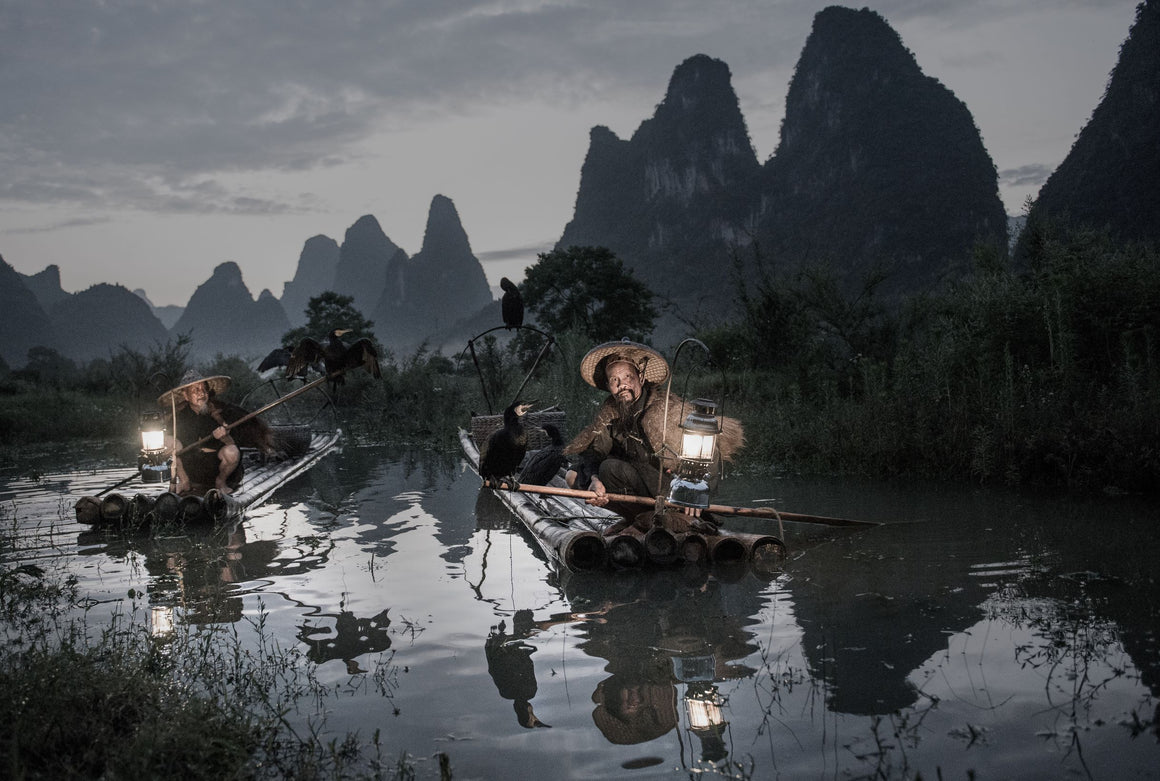 fishermen float bamboo rafts along the river using long wooden paddles