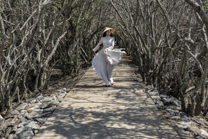 The traditional Ao Dai dress flaunting along the tree lined pass