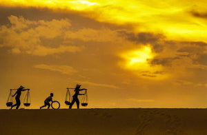 Champa women, walking with a kid creating silhouettes against the sky and soft sand