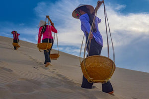 Champa women carrying goods on the silky soft sand dunes