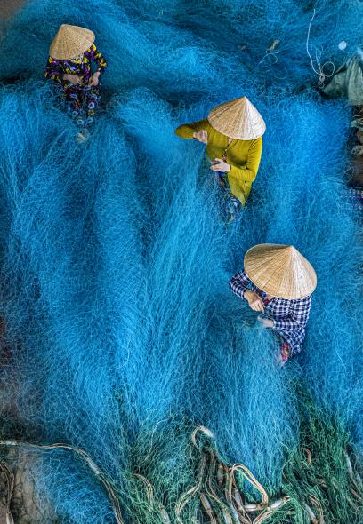 Women  engaging in weaving and repairing fishing nets