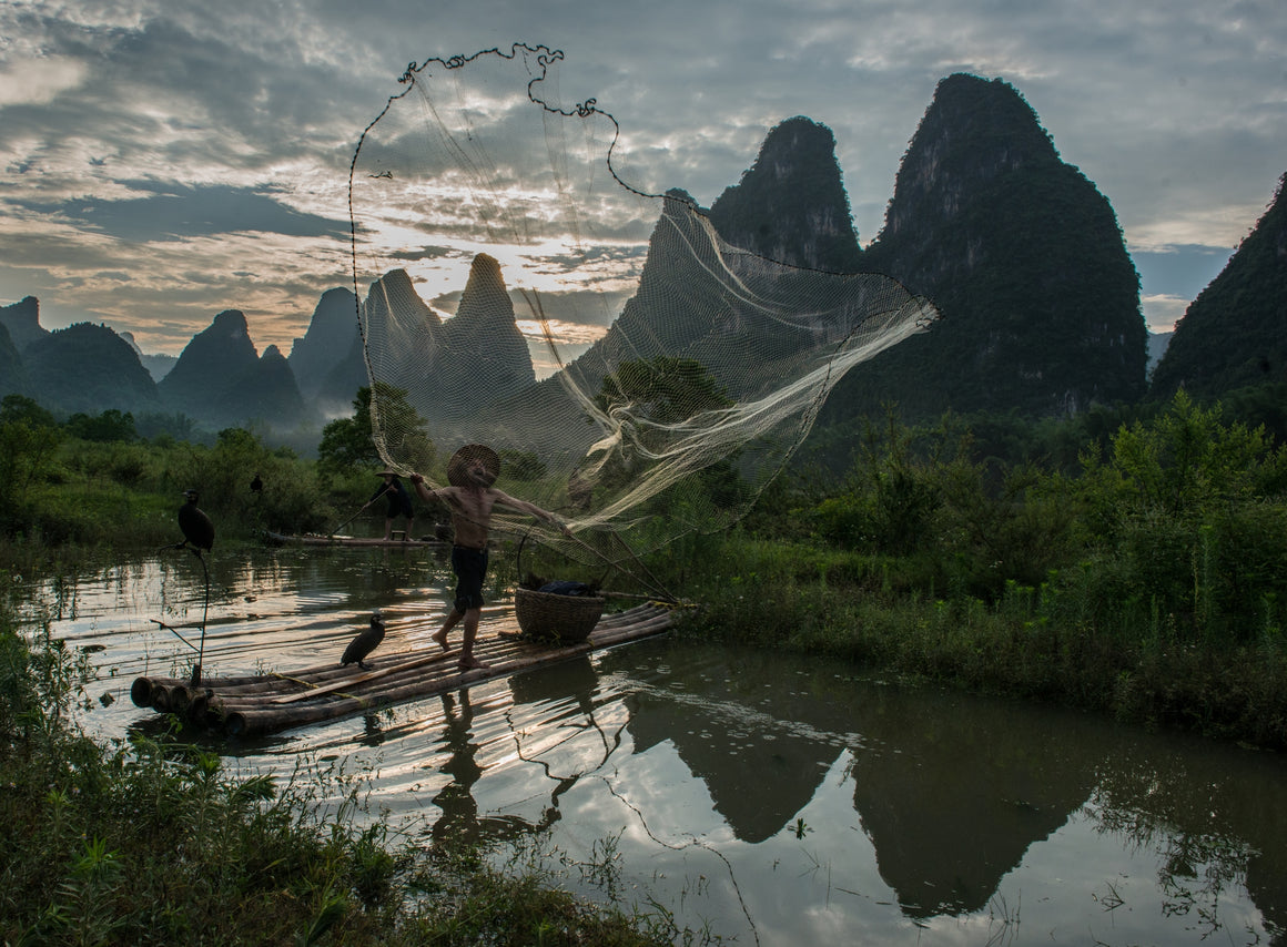 A fisherman throwing a giant fishing net into the water