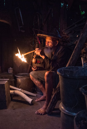 A senior Cormorant fisherman smoking an improvised cigar