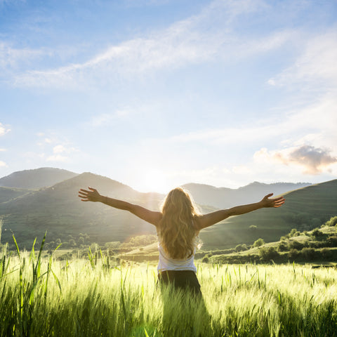 Woman Feeling Joyful in a field with mountains | Find Your Purpose in Life