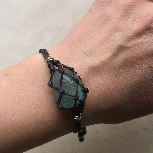 Macrame Crystal Pouch Bracelet with Fluorite, close up on woman's wrist.