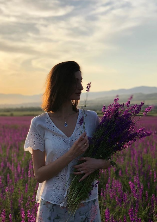 Woman holding flowers standing on a purple valley