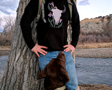 Man wearing Bison Hoodie from Naked Grit with dog by the river