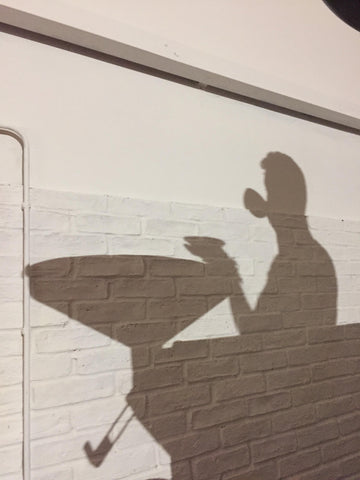 picture of a man drinking coffee cast in a shadow on the wall