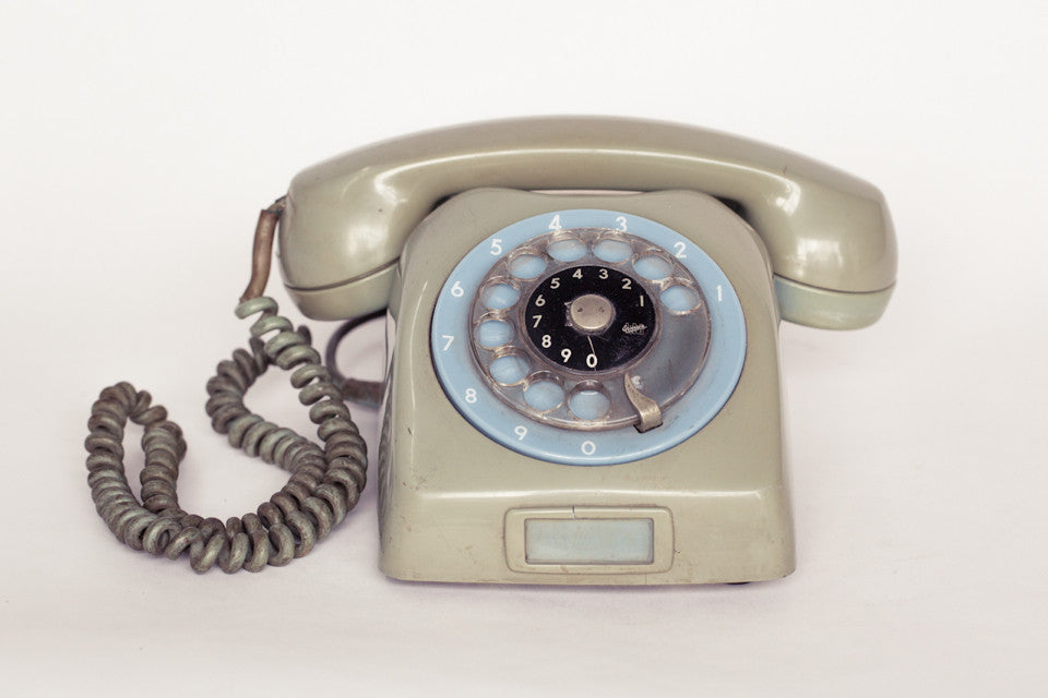1980s retro telephone in dirty green with baby blue dial.