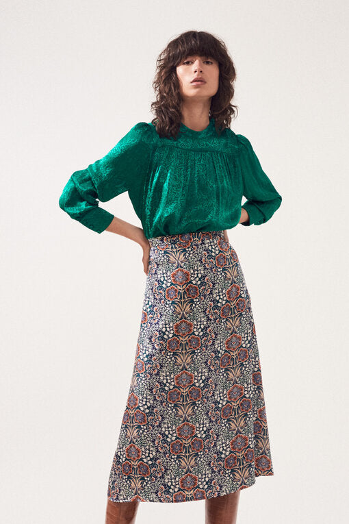Front of skirt on model wearing a green top and brown boots.