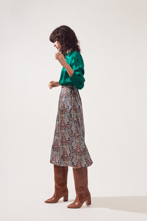 Side of skirt on model wearing a green top and brown boots.