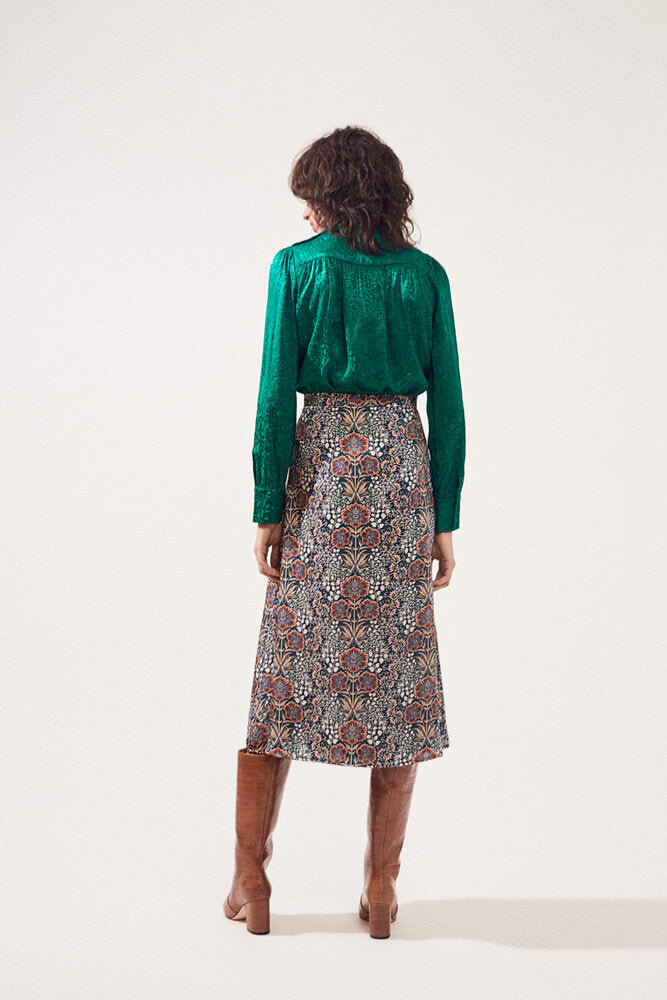 Back of skirt on model wearing a green top and brown boots.