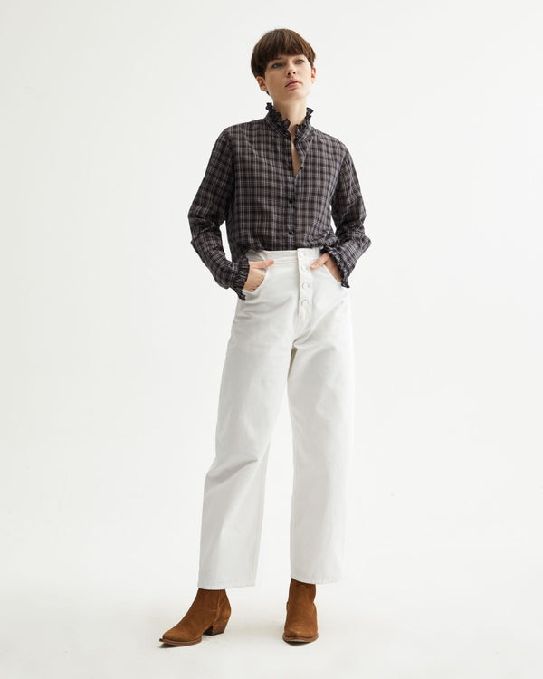 Front of pants on a model wearing a plaid shirt and boots