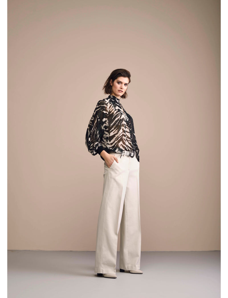 Side of blouse on model wearing white pants.
