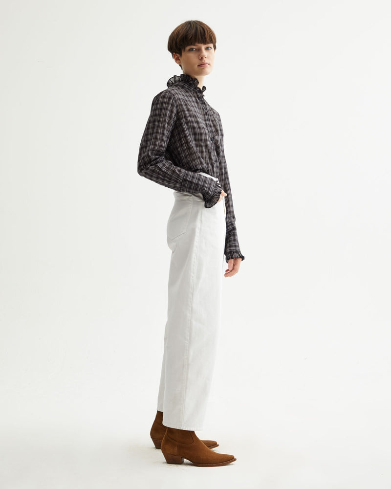 Side of pants on a model wearing a plaid shirt and boots.