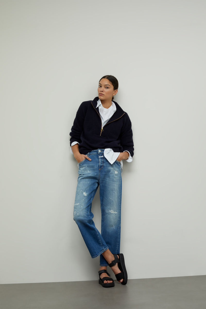 Model wearing jeans, white shirt and sweater.