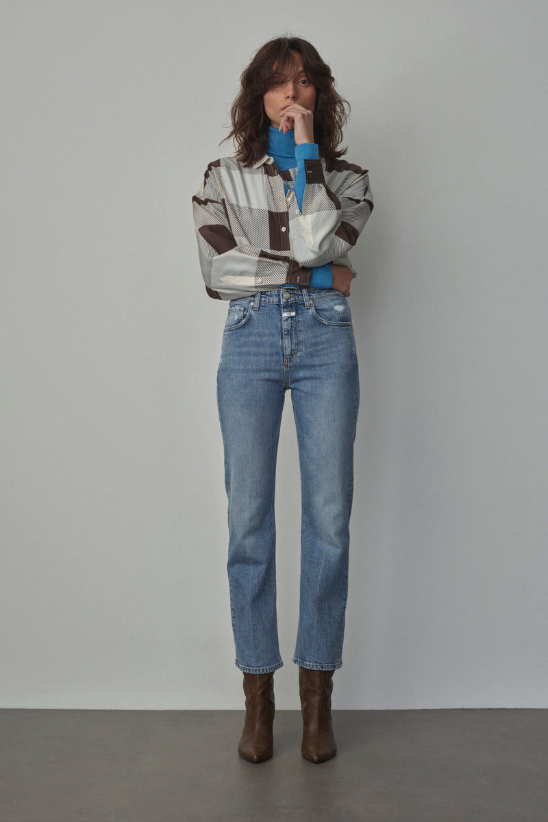 Styled look of model in turtleneck, silk blouse, jeans and boots.